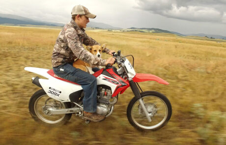 Young boy and his dog on a dirt bike