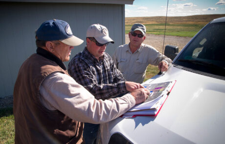 Three men looking at a map in a grasslands